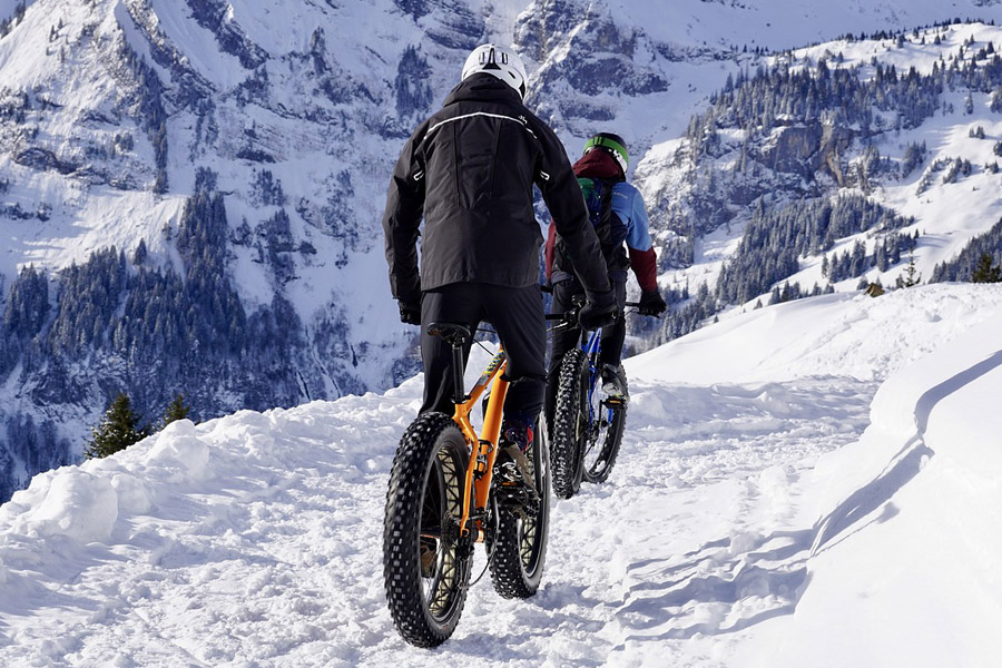 Two adult riding a mountain bike under snow weather