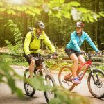 couple cycling together through the woods