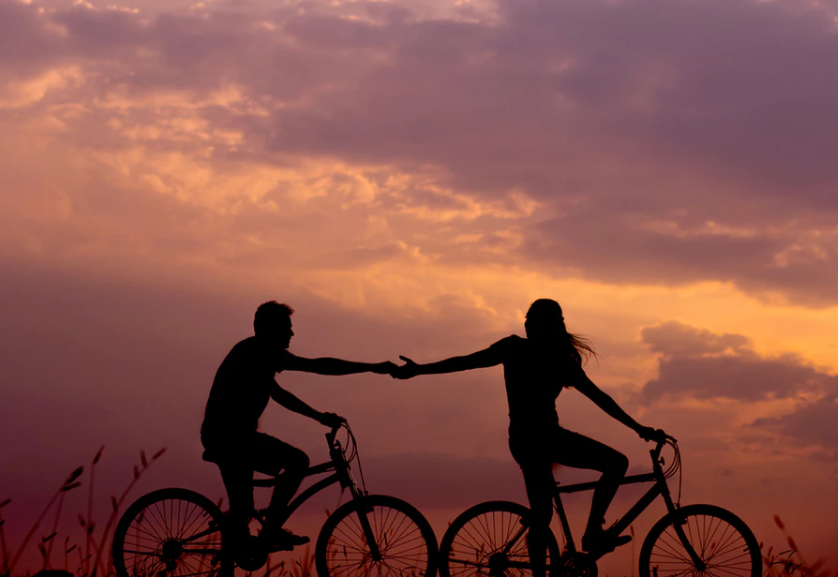 couple cycling together at sunset